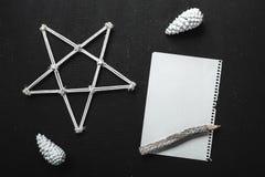 Décorations et feuille de vacances avec le list d'envie sur la table noire, style plat de configuration Composition de Noël Conce Photographie stock