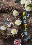 Décorations faites main de Pâques de configuration plate - guirlande des vignes avec des fleurs, lapins de papier, rubans sur un  Photos libres de droits