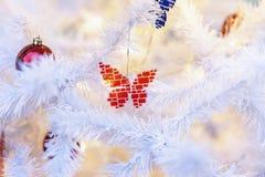 Décorations lumineuses d'un papillon en verre de mosaïque sur un arbre de Noël blanc Fond de fête pour la conception, l'espace de photo stock
