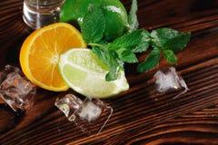 Décorations naturelles en gros plan de cocktail Chaux orange et saine juteuse, glaçons et feuilles en bon état sur un fond rustiq photos libres de droits