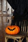 Décorations pour des vacances de Halloween - vieux chaise, battes d'origami et potiron Photo stock