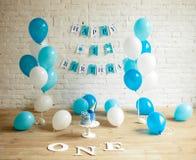 Décorations pour un anniversaire d'an avec les ballons, le gâteau et les inscriptions sur le mur et le plancher image stock