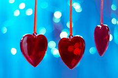 décorations rouges d'arbre de Noël sous forme de coeur sur un fond bleu des arbres de Noël avec le bokeh sur brouillé, scintillem Photos stock