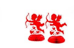 2 décorations rouges lumineuses de cupidon faisant face à gauche Photo stock