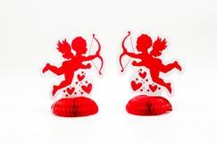 2 décorations rouges lumineuses de cupidon se faisant face Photos libres de droits