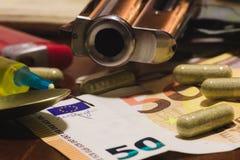 Décorum criminel avec des pilules et des drogues d'argent de revolver images stock