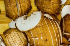 découpé en tranches avant de faire cuire le roi frais répand les champignons de paris sur un conseil en bambou Photographie stock
