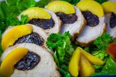 Découpé en tranches du pain de viande de l'échine avec le pruneau sur les feuilles de la laitue avec les pêches photos libres de droits