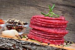 Découpé en tranches du salami avec des épices sur la planche à découper Photographie stock libre de droits