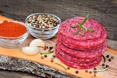 Découpé en tranches du salami avec des épices sur le fond rustique Photos libres de droits
