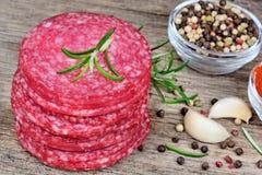 Découpé en tranches du salami et des épices sur la table en bois Photo stock