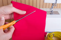 Découpage du tissu avec des ciseaux Images stock