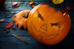 Découpage d'un potiron pour Halloween, décoration d'automne d'étameur ambulant sur un b Photographie stock