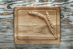 Découpage des oreilles de blé de conseil sur la surface en bois de vintage Photographie stock libre de droits