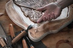 Découpage du bois, main d'un artisan pour l'outil, Photographie stock