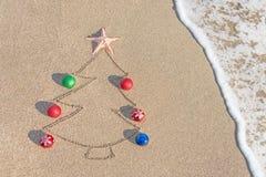 Découpe d'arbre de Noël avec les décorations, l'étoile et la vague sur la plage Photographie stock
