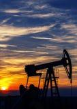 Découpe fonctionnante de puits de pétrole et de gaz, décrite sur le coucher du soleil Photos stock