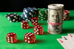 Découpez, en jouant des cartes, des jetons de poker et tordu 100 billets d'un dollar dessus Photo stock