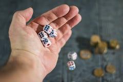 Découpez la chute hors de la main d'un homme sur une table en bois noire avec les pièces de monnaie d'or Photo stock
