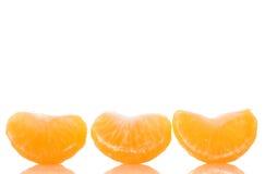 Découpez les sections en tranches de la mandarine mûre d'isolement au-dessus du blanc Photos stock
