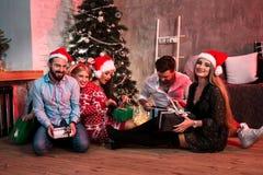 Décrivez montrer le groupe d'amis avec des cadeaux de Noël sur la partie à la maison Photo libre de droits