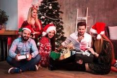 Décrivez montrer le groupe d'amis avec des cadeaux de Noël sur la partie à la maison Photo stock