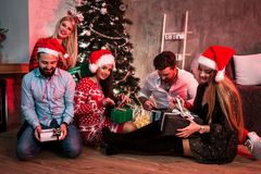 Décrivez montrer le groupe d'amis avec des cadeaux de Noël sur la partie à la maison Photos libres de droits