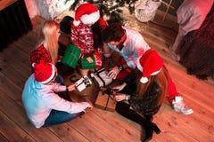 Décrivez montrer le groupe d'amis avec des cadeaux de Noël sur la partie à la maison Image stock