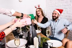 Décrivez montrer le groupe d'amis célébrant Noël à la maison et donnant des présents entre eux Photo stock