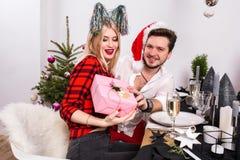 Décrivez montrer le groupe d'amis célébrant Noël à la maison et donnant des présents entre eux Images stock