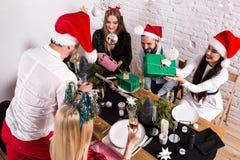 Décrivez montrer le groupe d'amis célébrant Noël à la maison et donnant des présents entre eux Image stock