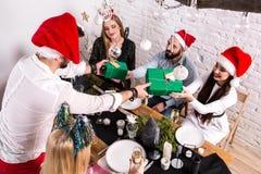 Décrivez montrer le groupe d'amis célébrant Noël à la maison et donnant des présents entre eux Photographie stock