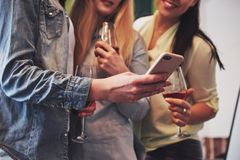Décrivez présenter un groupe heureux de amie avec le vin rouge Ensemble ils voient une photo sur un smartphone Images stock