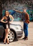 Décrivez un homme essayer de fixer la voiture à son amie et lookin Images libres de droits