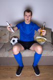Défenseur émotif du football regardant la TV avec de la bière et des pommes chips Images libres de droits