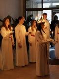 Défilé de Lucia avec les filles et les garçons chanteurs dans le holdin blanc de robes Images stock