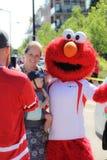 Défilent avec le costume d'Elmo et bébé et mère Image stock