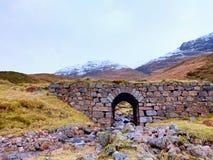 Dégagez la rivière incurvée de courant au-dessous du vieux pont pierreux Chemin de moutons de montagne Photographie stock libre de droits