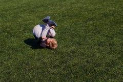 Dégringolades de bébé sur la couverture artificielle verte dehors photographie stock
