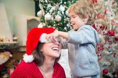 Déjeme ayudarle con el sombrero de Santas Fotografía de archivo libre de regalías