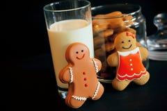 Déjeunent avec la fille et le garçon heureux de pain d'épice, et le verre de lait Image stock