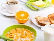 Déjeuner avec les cornflakes, le pain grillé, l'orange et le café Photos stock