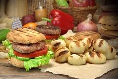 Déjeuner avec les hamburgers grillés par BBQ faits maison sur la table de cuisine Images stock
