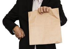 Déjeuner brun de sac de papier de participation d'homme d'affaires (partager, donnant), d'isolement sur le fond blanc Photographie stock libre de droits