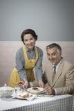 Déjeuner de portion de femme de vintage à son mari Image stock
