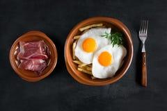 Déjeuner espagnol traditionnel - les oeufs au plat avec des pommes frites, porc traité découpe le jamon en tranches Photo stock