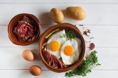 Déjeuner espagnol traditionnel - les oeufs au plat avec des pommes frites, porc traité découpe le jamon en tranches Image libre de droits