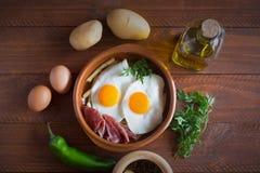 Déjeuner espagnol traditionnel - les oeufs au plat avec des pommes frites, porc traité découpe le jamon en tranches Images stock