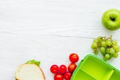 Déjeuner fait maison avec la pomme, la tomate et le sandwich dans le panier-repas vert Photos libres de droits