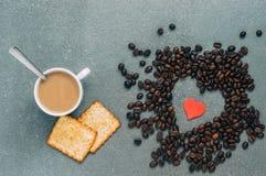 Déjeuner pour des amoureux Grains de café sous forme de coeur, tasse de café et biscuits sur un fond gris, vue supérieure Image stock